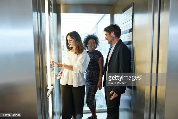 business people taking elevator in modern office building - elevador - fotografias e filmes do acervo