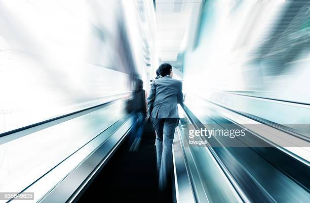 business people taking escalator blur motion,business on the move