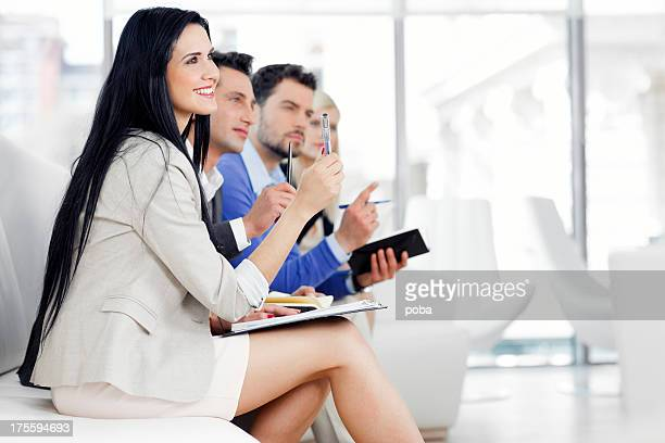 Business people taking notes and  raising hands in seminar