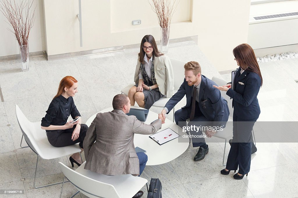 Business people talking and shaking hands shot from above : Stock Photo