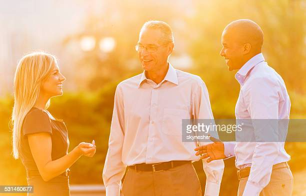 Business people talking at sunset.