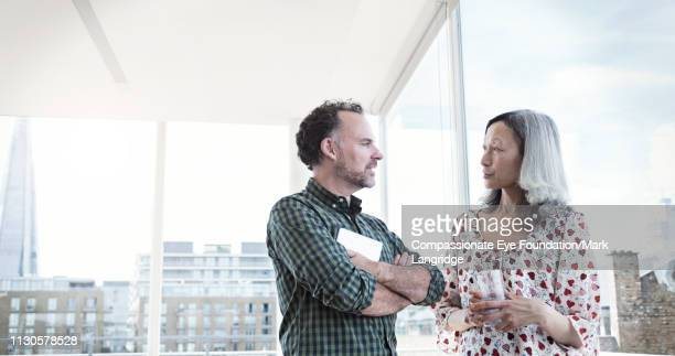 business people talking by window in modern office - vanguardians stock pictures, royalty-free photos & images