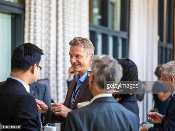 business people talking during coffee break at conference - unterhaltungsveranstaltung stock-fotos und bilder