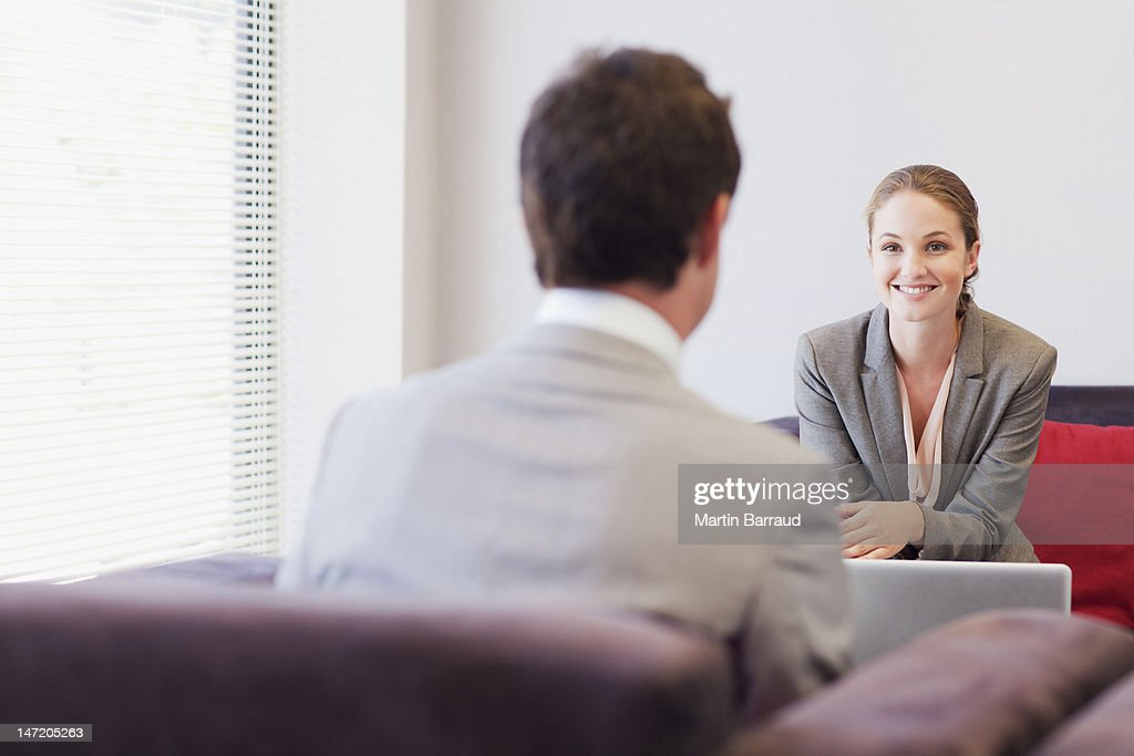 Business people talking face to face in lobby : Stock Photo