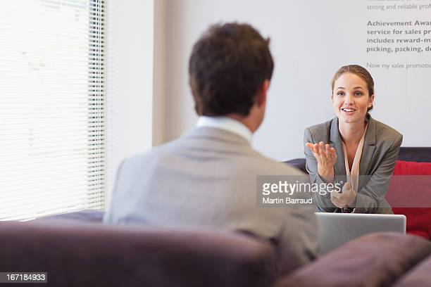 business people talking face to face in lobby - interview stock pictures, royalty-free photos & images