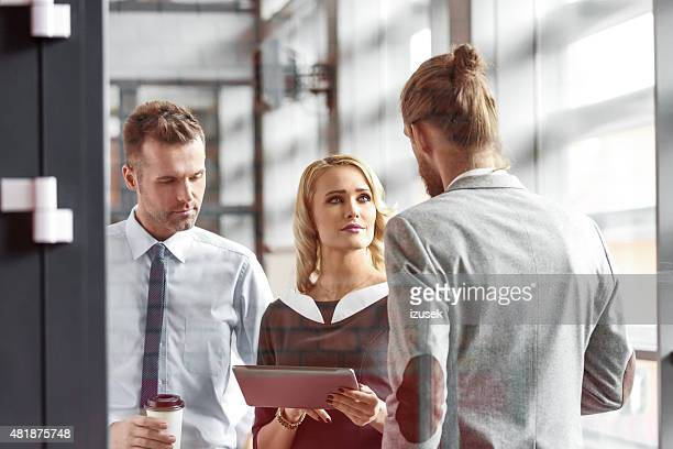 business people talking in an office, woman holding digital tablet - izusek stock pictures, royalty-free photos & images