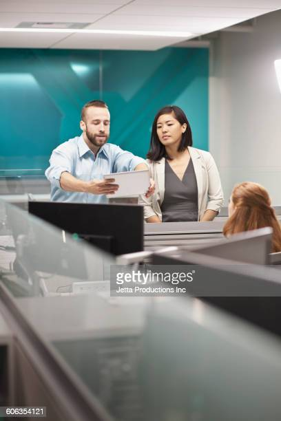 Business people talking in cubicle