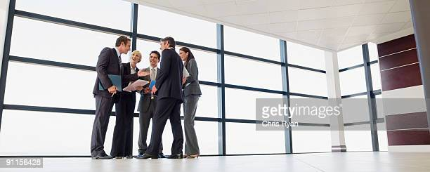 business people talking in lobby - five people stock pictures, royalty-free photos & images