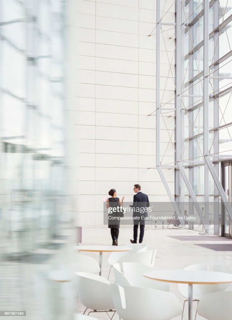 Business people talking in modern lobby : Stock Photo
