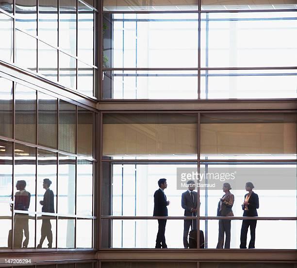 話しているビジネス人々の現代的なオフィスの廊下