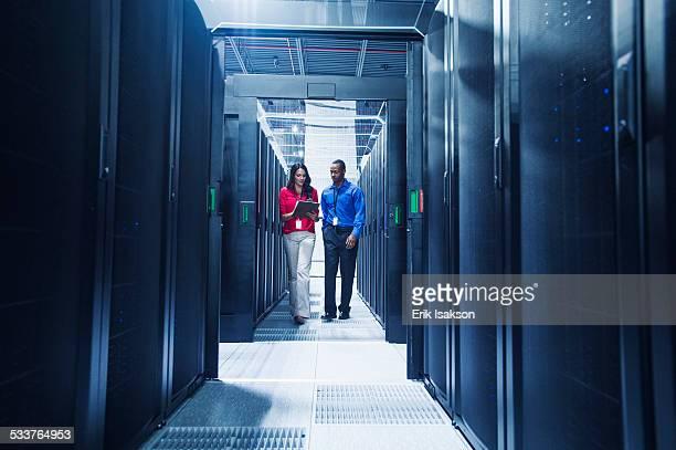 Business people talking in server room