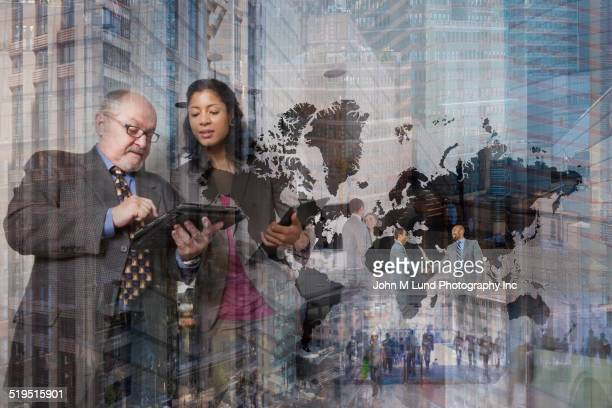Business people talking near world map and cityscape