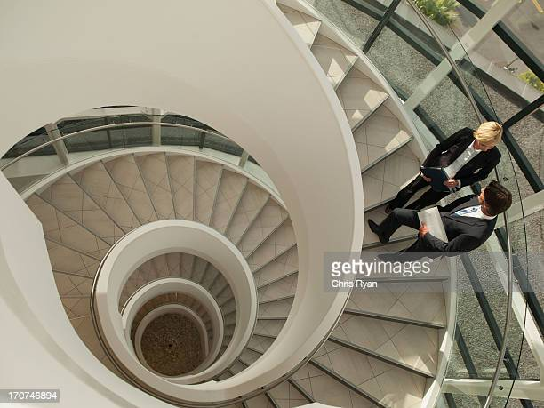 Business people talking on circular staircase