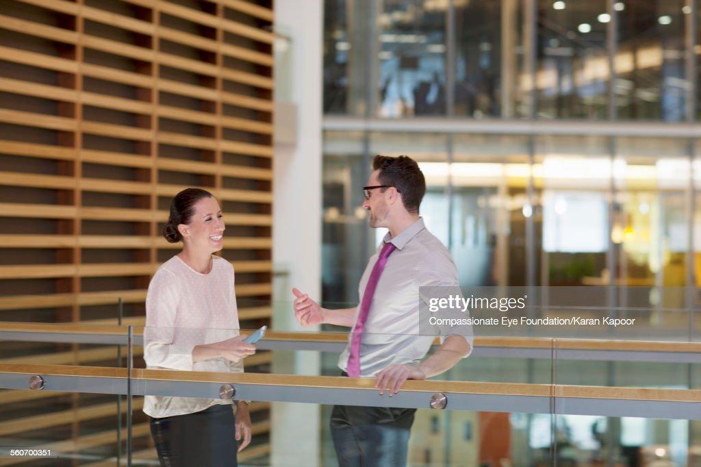 Business people talking on elevated walkway : Stock Photo