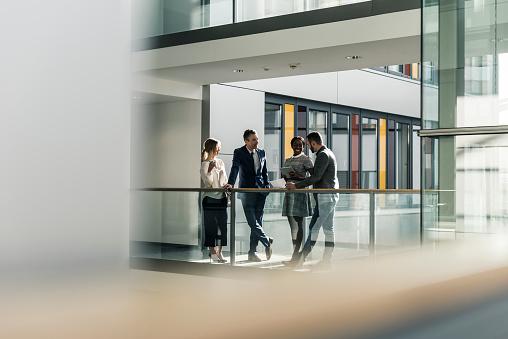 Business people talking on office floor - gettyimageskorea