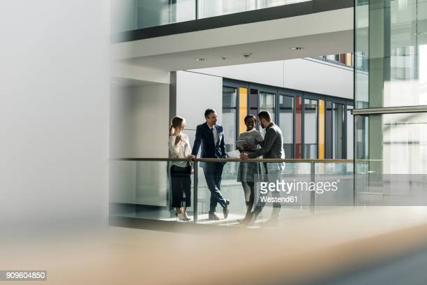 business people talking on office floor - distant stock pictures, royalty-free photos & images