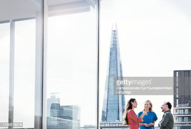 business people talking on sunny urban rooftop - ideas stock pictures, royalty-free photos & images