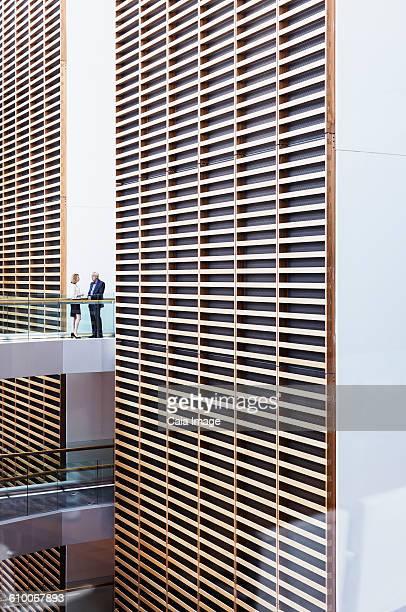 Business people talking on walkway in modern office atrium