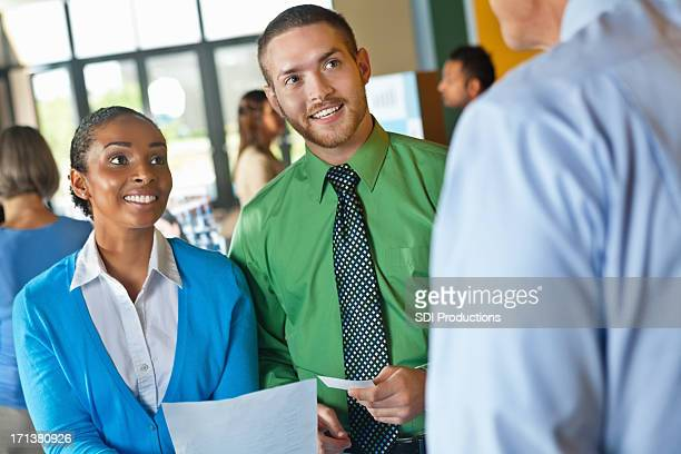 business people talking to potential employees at a job fair - job fair stock pictures, royalty-free photos & images