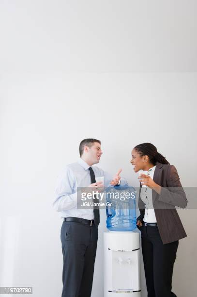 business people talking together at water cooler - femme fontaine photos et images de collection