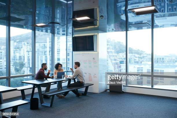 business people talking while having coffee break in the office - picnic table stock pictures, royalty-free photos & images