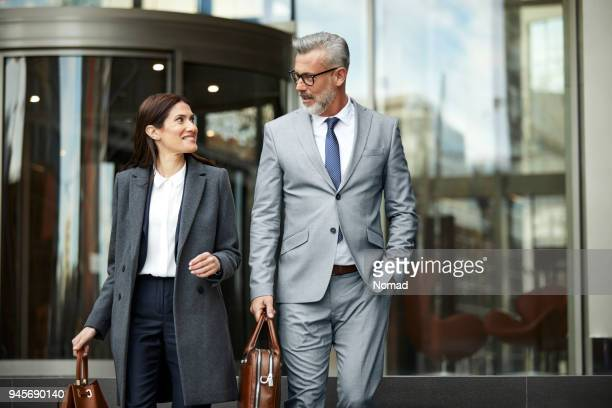 business people talking while leaving office - hands in pockets stock pictures, royalty-free photos & images