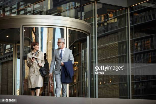 business people talking while leaving workplace - formal businesswear stock pictures, royalty-free photos & images