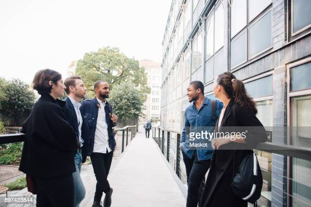 business people talking while standing on walkway by cafe - five people stock pictures, royalty-free photos & images