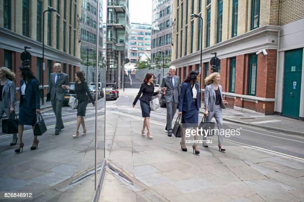Business people talking while walking on sidewalk
