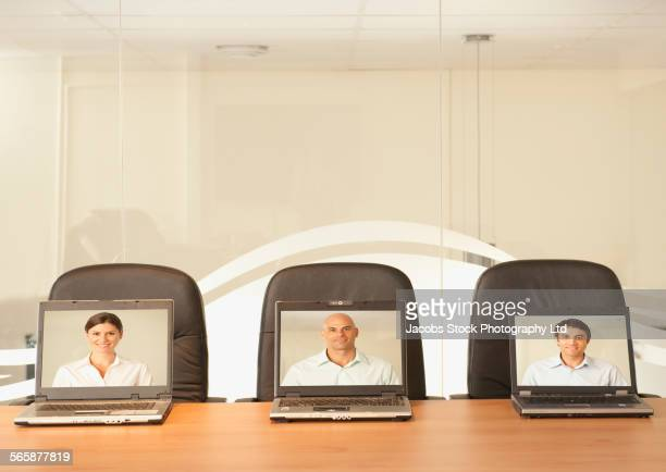 Business people teleconferencing on laptops in office
