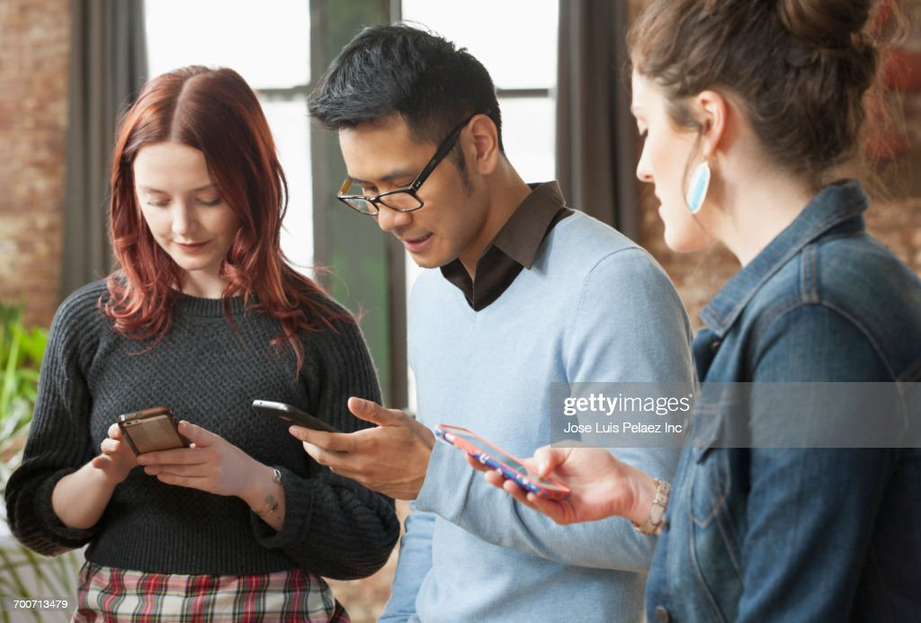 Business People Texting On Cell Phones In Office Stock Photo