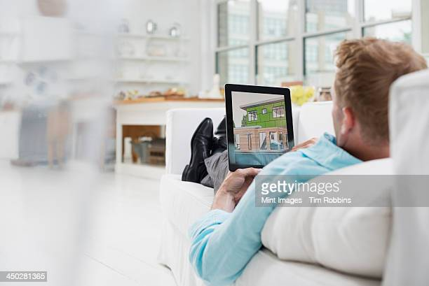 business people. the office in summer. a man lying on a sofa, in comfort, in a quiet airy office environment. using a digital tablet. - bank zitmeubels stockfoto's en -beelden