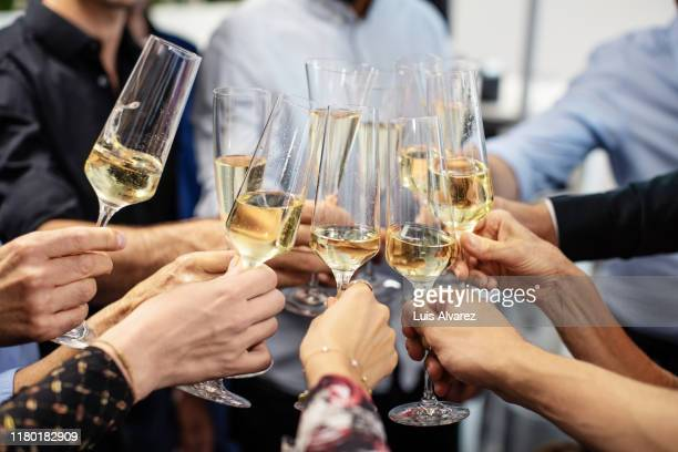 business people toasting champagne flutes in office - toost stockfoto's en -beelden