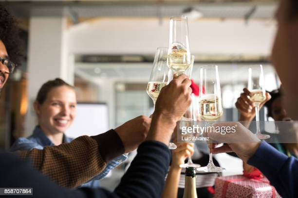 business people toasting champagne flutes while celebrating christmas - festeggiamento foto e immagini stock