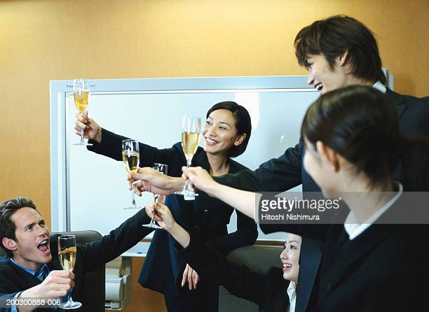 Business people toasting champagne, smiling