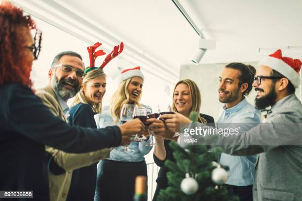 business people toasting with red wine at workplace - christmas party stock photos and pictures