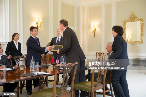 business people trading plaques in meeting - global awards stock pictures, royalty-free photos & images