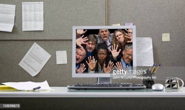 Business people trapped in computer monitor