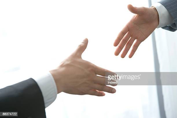 Business people trying to shake hand