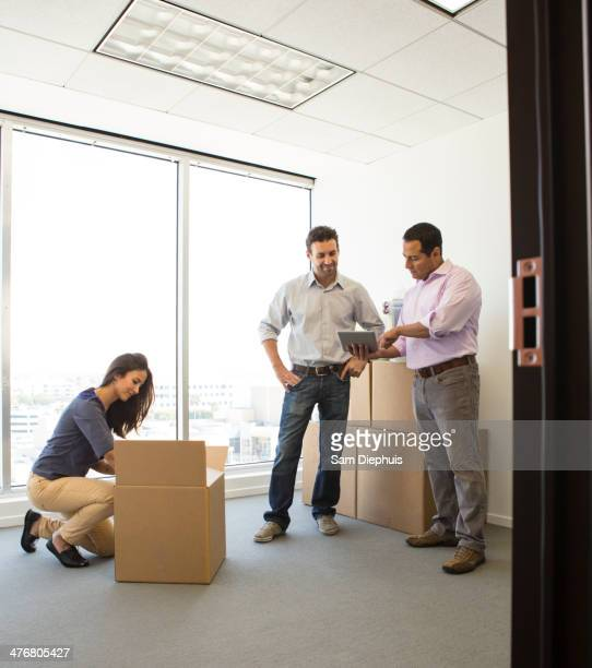 business people unpacking in new office - loader reading stock pictures, royalty-free photos & images