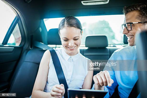 Business people using a tablet in a car