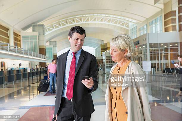 Business people using cell phone in airport