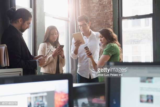 Business people using cell phones and digital tablets in office