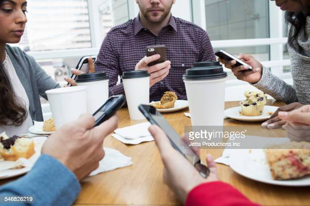 Business people using cell phones at working breakfast