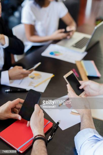 Business people using cell phones during a meeting in office