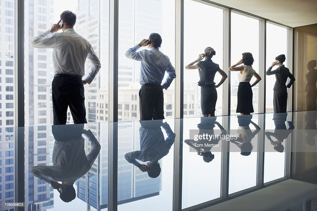 Business people using cell phones in conference room : Stock Photo