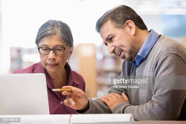 Business people using computer in library