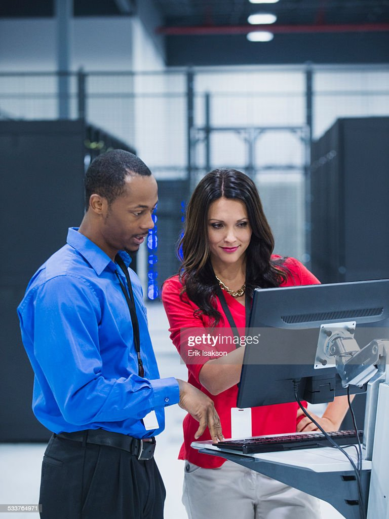 Business people using computer in server room : Stock Photo
