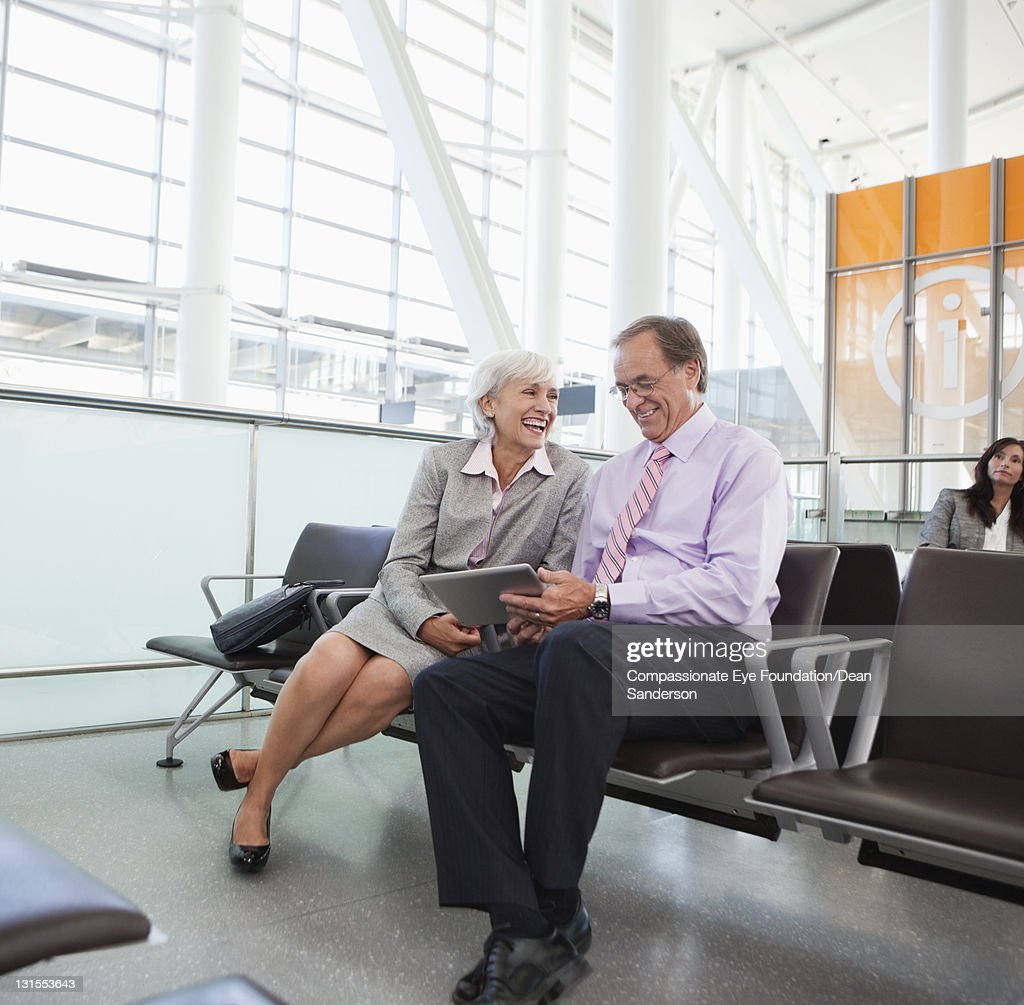 Business people using digital tablet at airport : Stock Photo