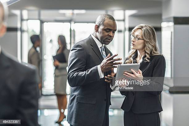 business people using digital tablet in office - formal businesswear stock pictures, royalty-free photos & images